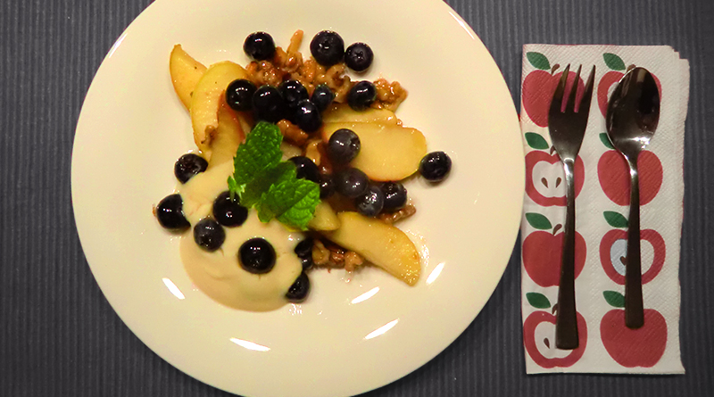 Gebratene Apfelspalten, karamellisierte Walnüsse und frische Blaubeeren auf Honigschmand
