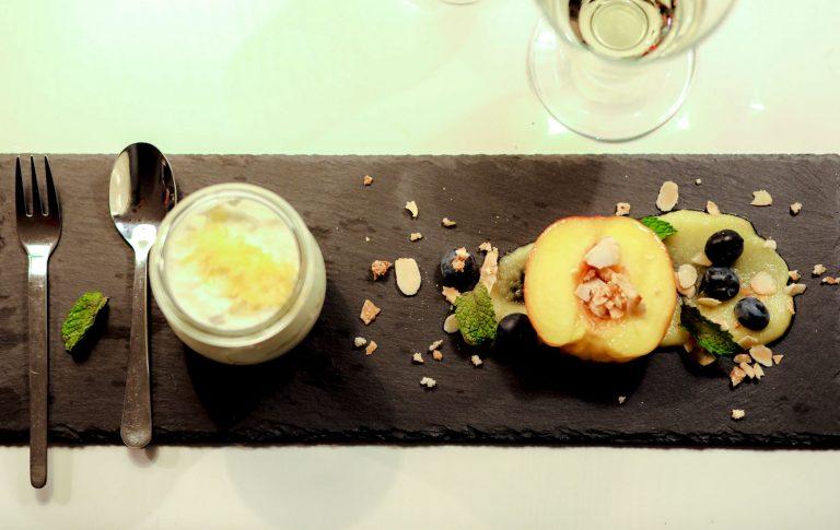 Zitronen-Posset mit gegrilltem Pfirsich und Mandelkrokant auf Mangopüree
