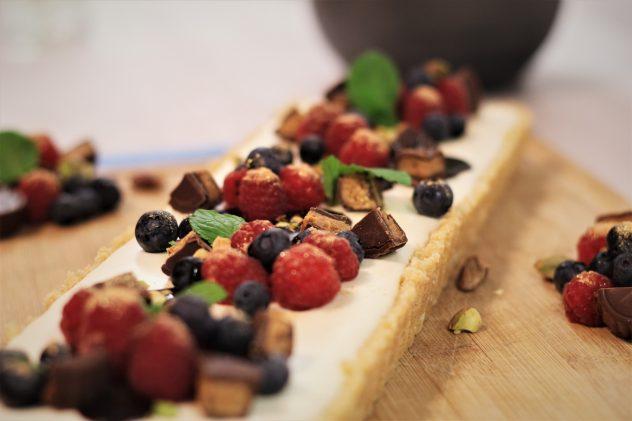 Cheesecake mit Blaubeeren und Himbeeren und Peanut Butter Caramels